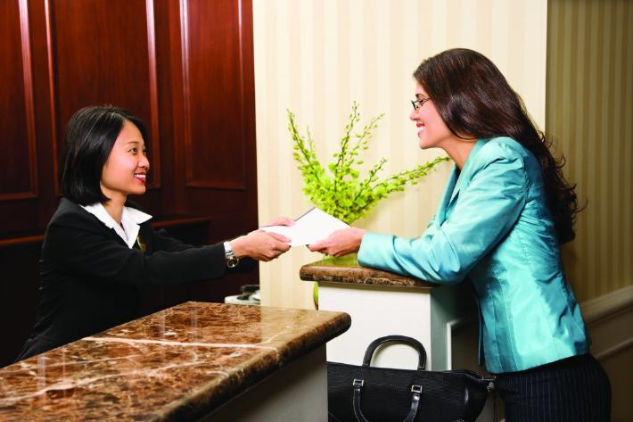 Smiling hotel receptionist helping a guest